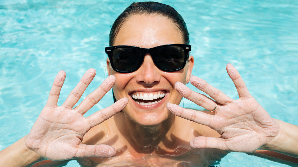 Swimming woman with wrinkled fingers