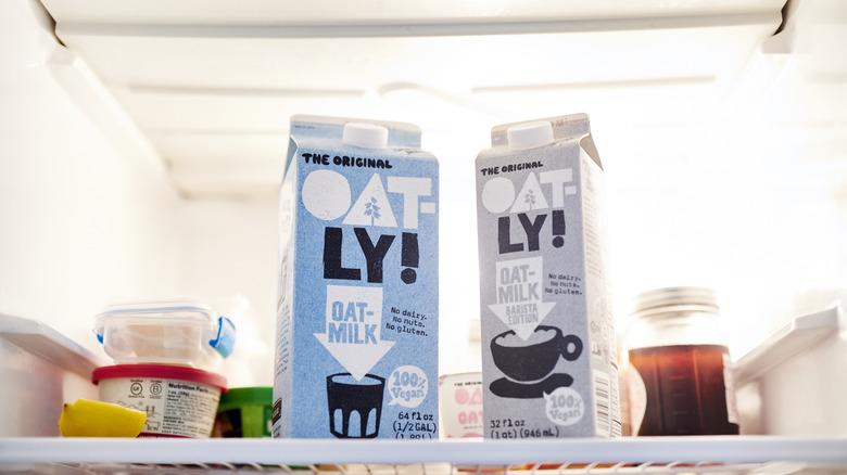 Two cartons of Oatly's oat milk in a fridge