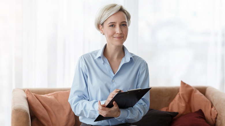 professional psychologist sitting on a sofa with a clipboard