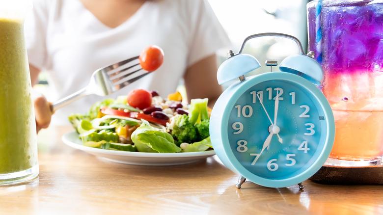 woman eating salad next to clock