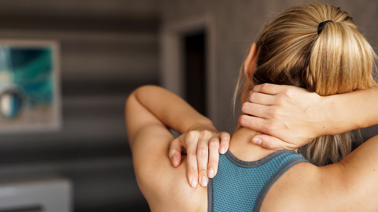 young woman feeling pain in her neck and shoulders