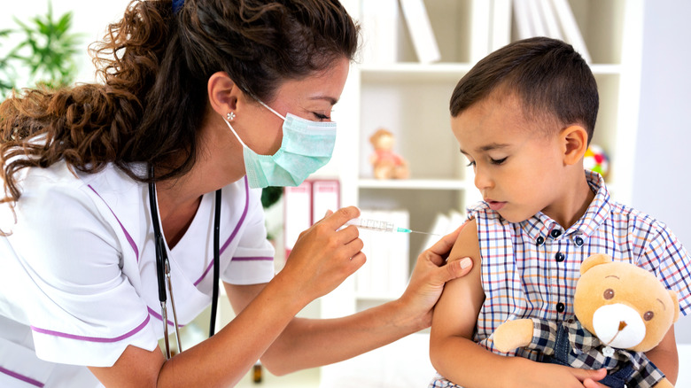 Doctor giving child vaccine shot in arm