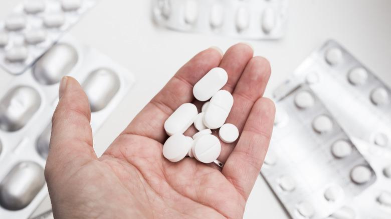 hand holding white pills