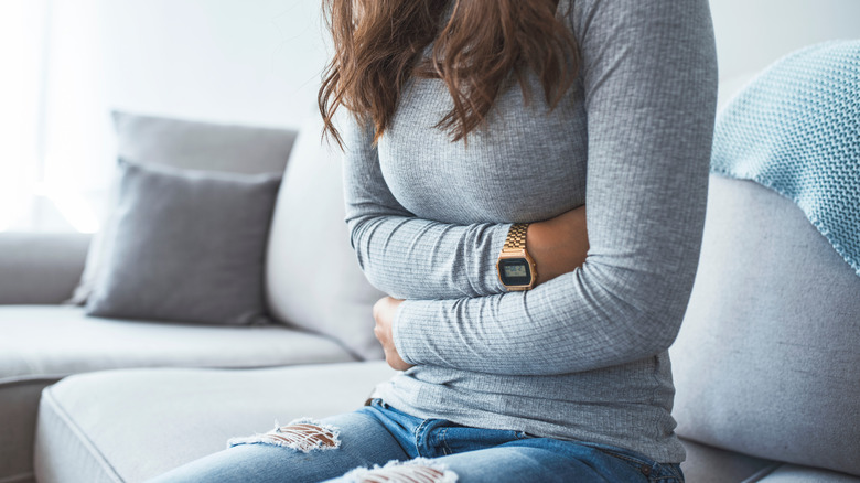 Close-up of woman on the couch holding her abdomen in pain