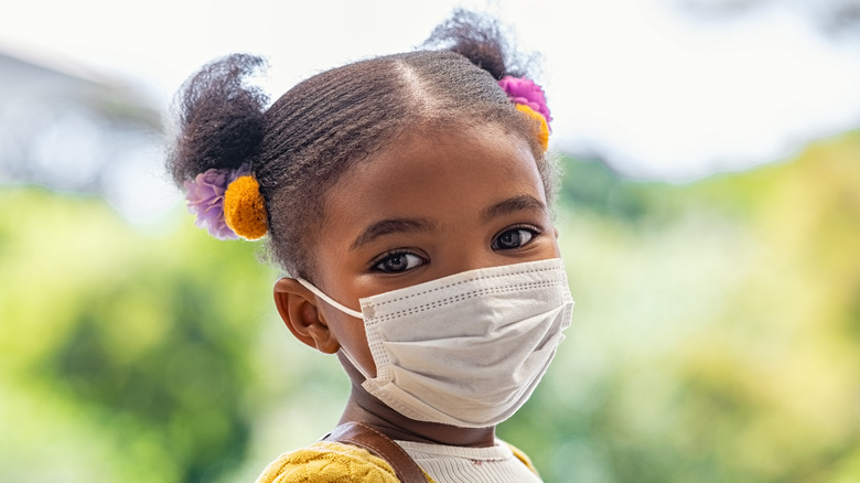 Smiling little girl with school backpack and protective face mask