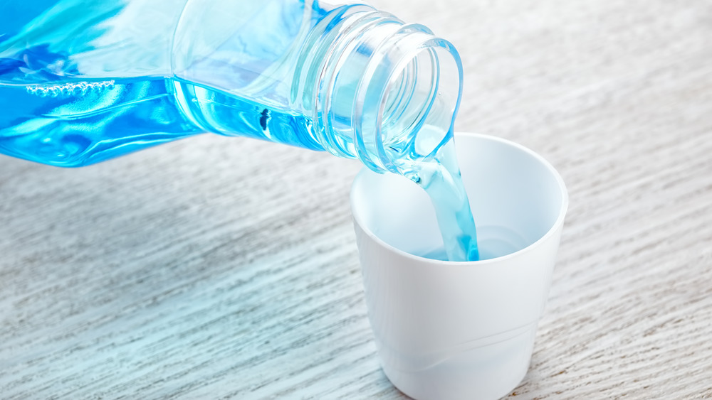 Blue mouthwash pouring from a plastic bottle into a small white cup