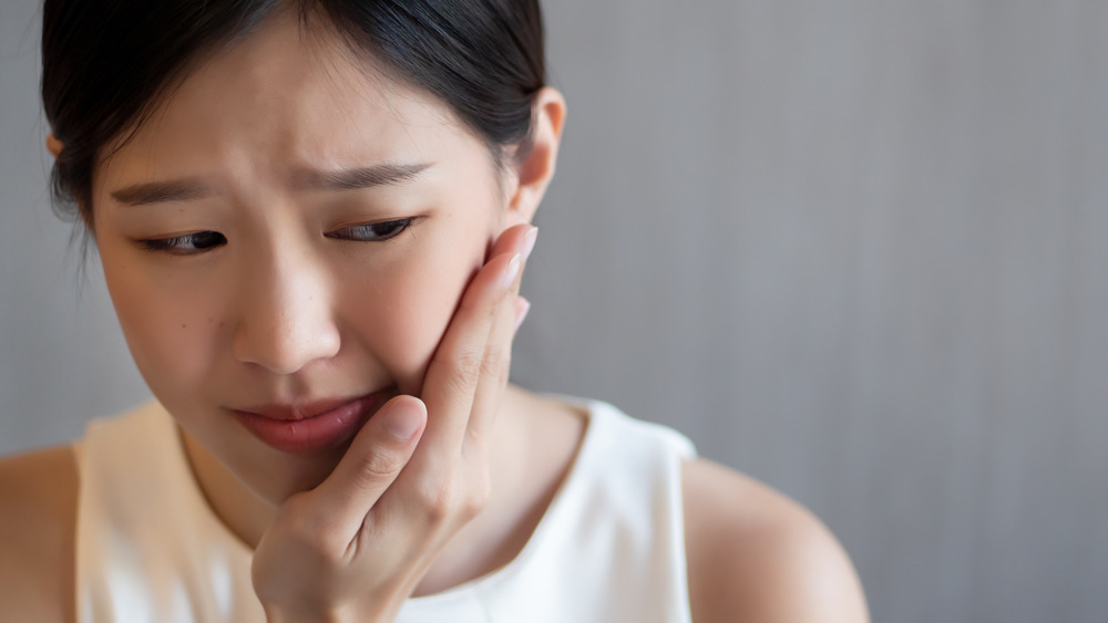 Woman holding the side of her mouth with tooth pain