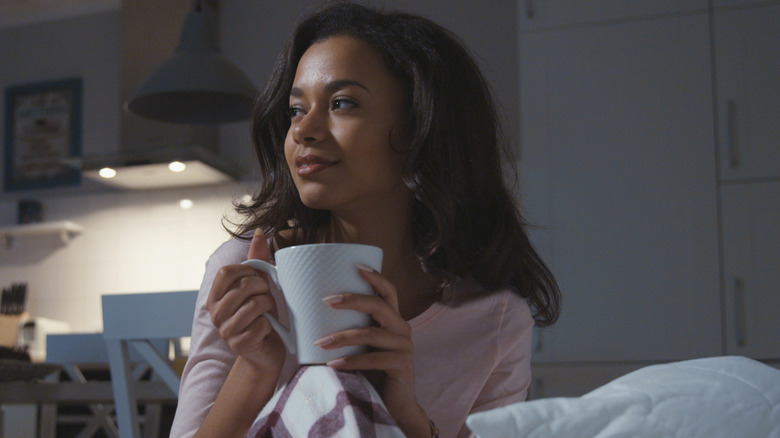 woman drinking tea in dark bedroom