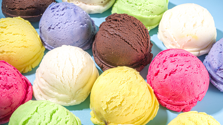 Different colors of ice cream in scoops next to each other on a light blue-colored surface