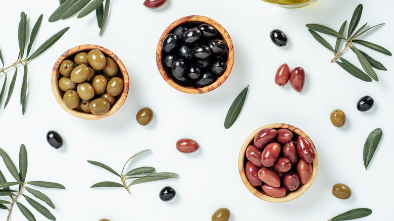 A variety of olives in wooden bowls against a white background decorated with olives and olive leaves