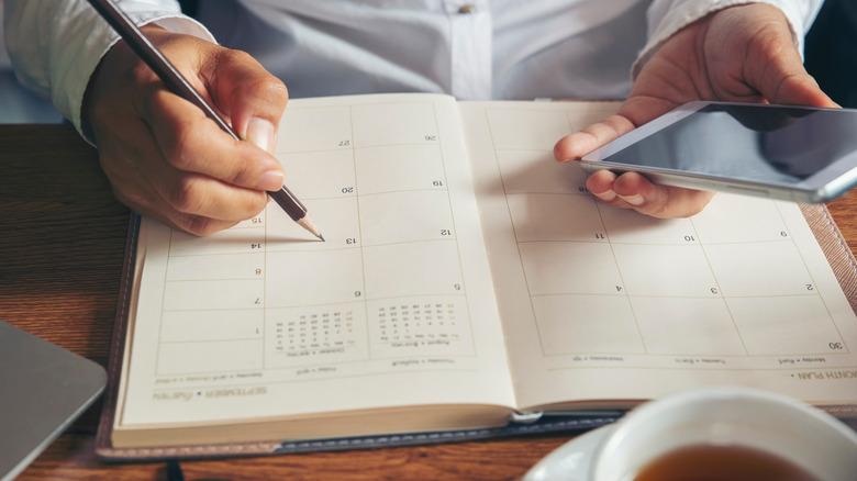 Someone scheduling in a calendar