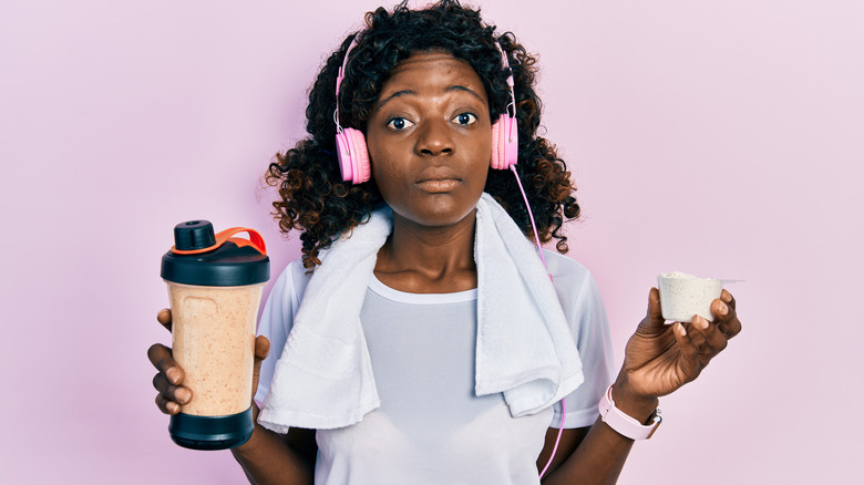 Surprised woman holding protein shake and powder
