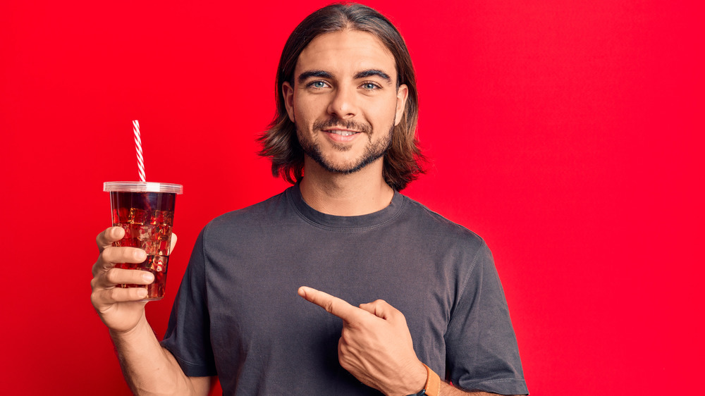 man pointing at soda