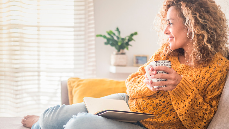 a woman on her couch with a coffee cup and book