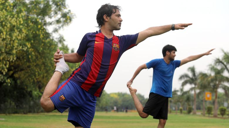 men balancing on one leg