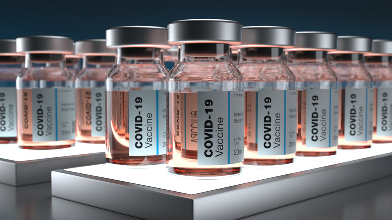 Close up of several vials labeled COVID-19 vaccine