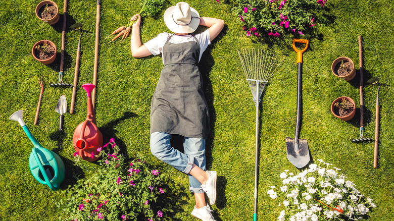 woman relaxing in her garden surrounded by gardening tools