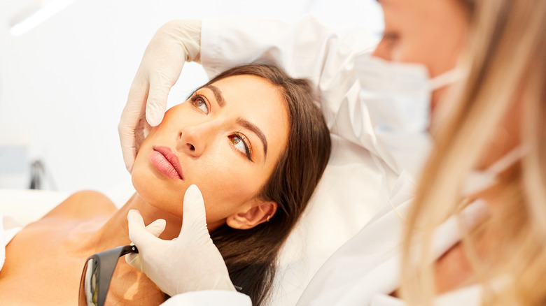 A woman gets advised on facelift surgery