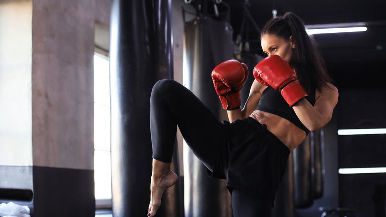A woman is doing a kickboxing workout