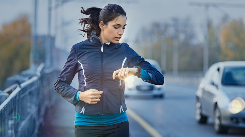 Woman running and looking down at her watch
