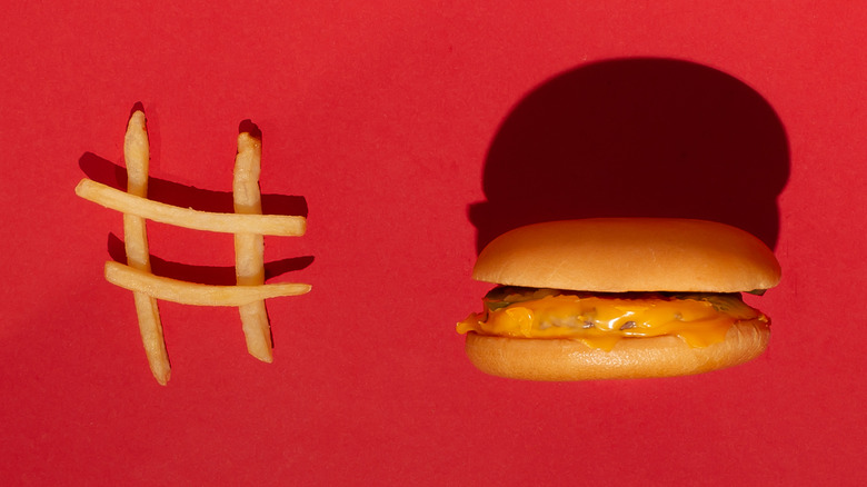 hashtag made of french fries and a cheeseburger against all red background