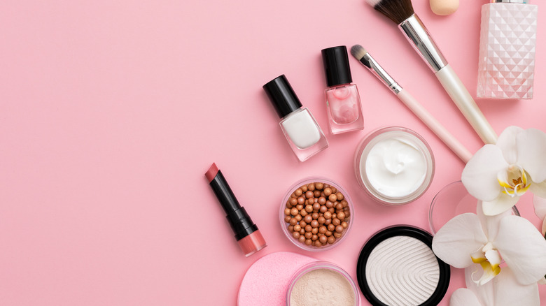 variety of makeup items on a pink background with flower