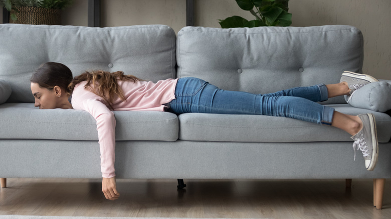 A young woman fully dressed lying face down on her couch