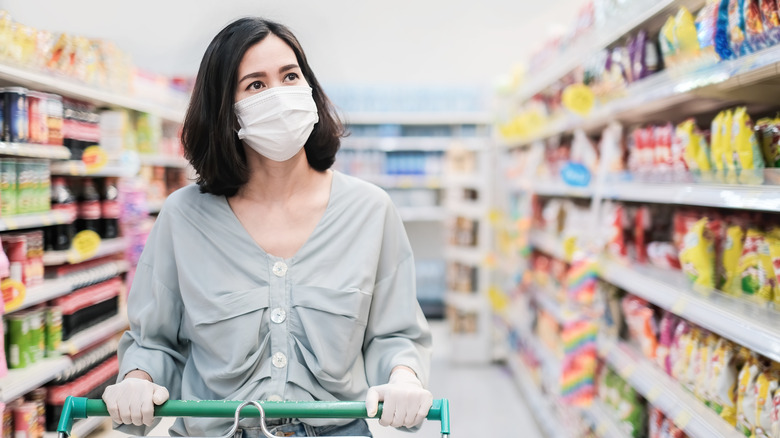 A woman grocery shops while wearing a mask