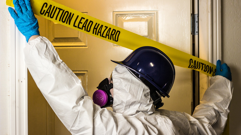 Man in a hazard suit positing a warning across a door painted with lead-based paint