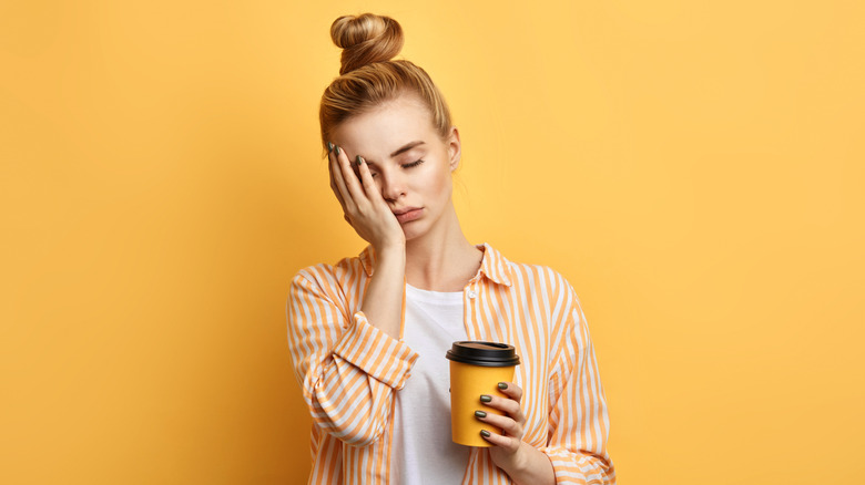 Woman hold cup of coffee with eyes closed and hand on face