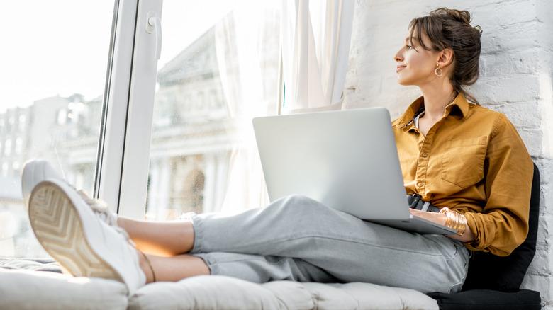 Woman working on laptop by window