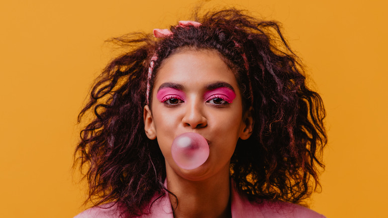 Woman with pink eyeshadow blowing a pink bubble gum bubble on orange background