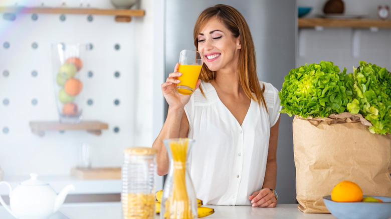 A woman is drinking a glass of orange juice