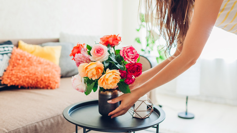 Woman with vase of roses on table