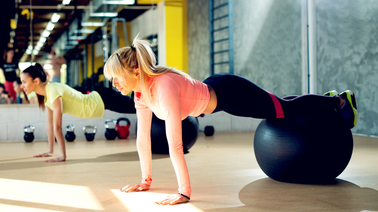 Women doing push-ups with stability balls in gym