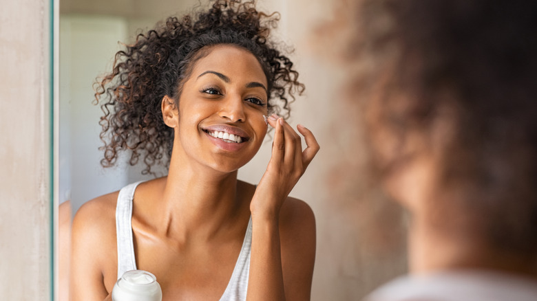 A woman is moisturizing her face