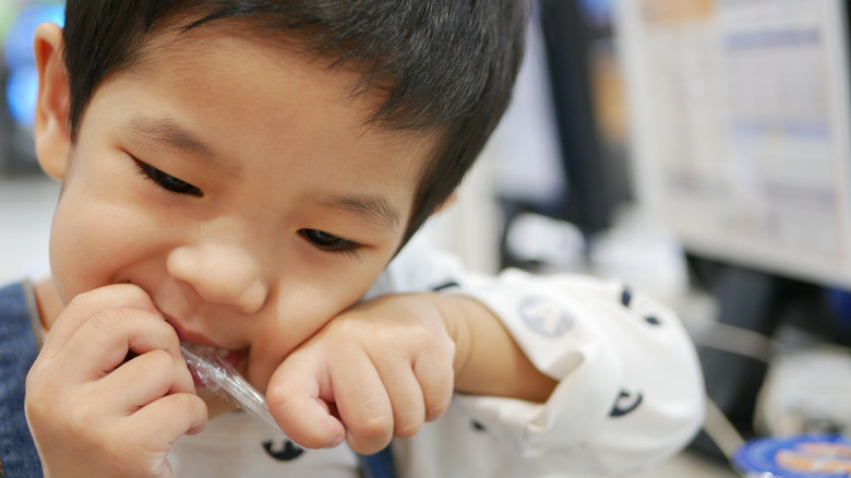 little boy tearing at a straw package with his teeth