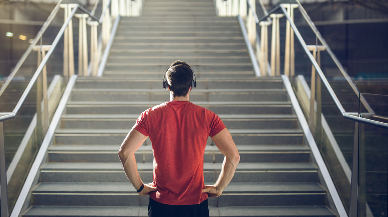 Man with headphones looking at staircase