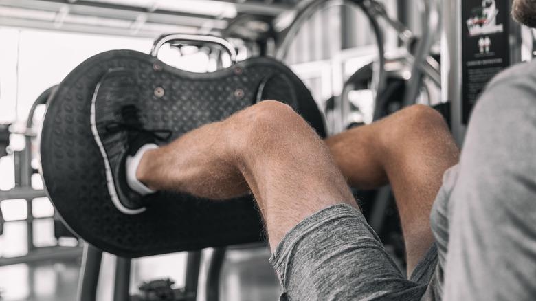 muscular legs using leg press machine