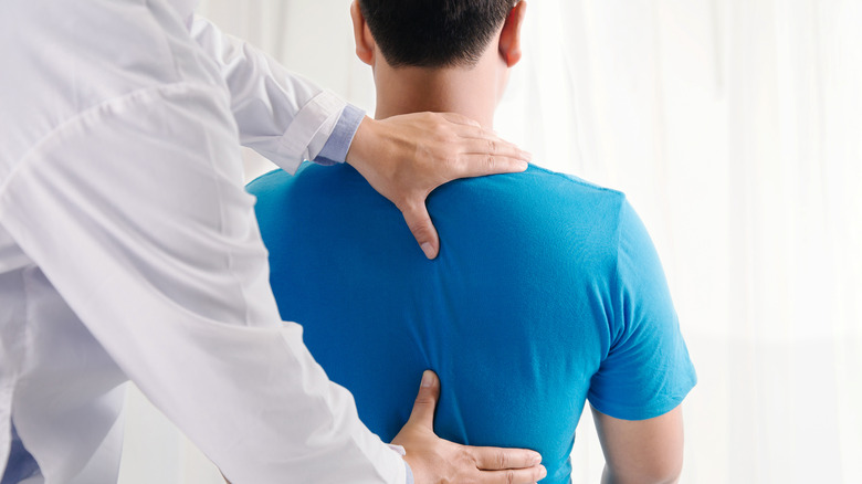 Doctor working with man's back