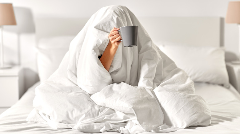 woman hiding in her comforter holding out a coffee cup
