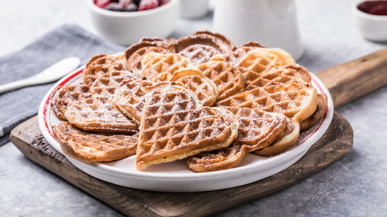 A plate of heart-shaped waffles on a table