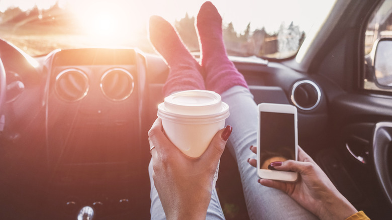 Person with long red nails wearing jeans and purple socks and holding a paper coffee cup and an iphone has their feet propped up on the dashboard of a car. The sun is shining directly into the windshield.
