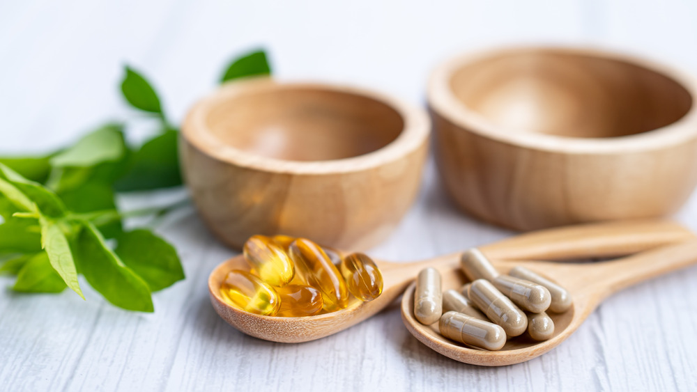 Vitamin supplements on wooden spoons