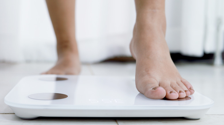 Close up of woman's feet stepping on a scale