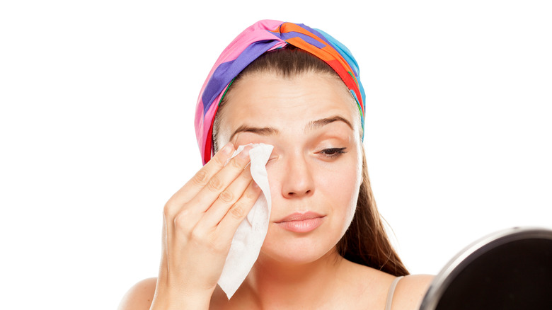 woman cleaning face with makeup wipes