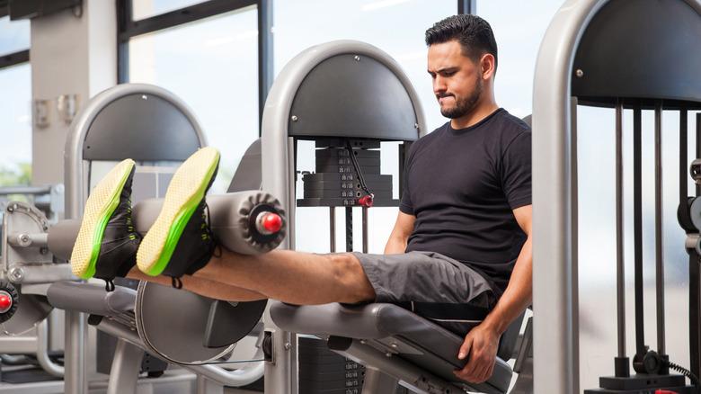 A man uses a leg extension machine