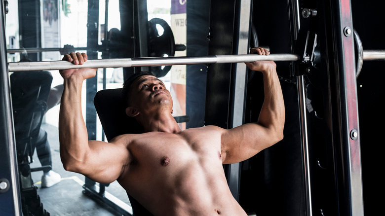 A man uses a Smith machine to lift a barbell over his head