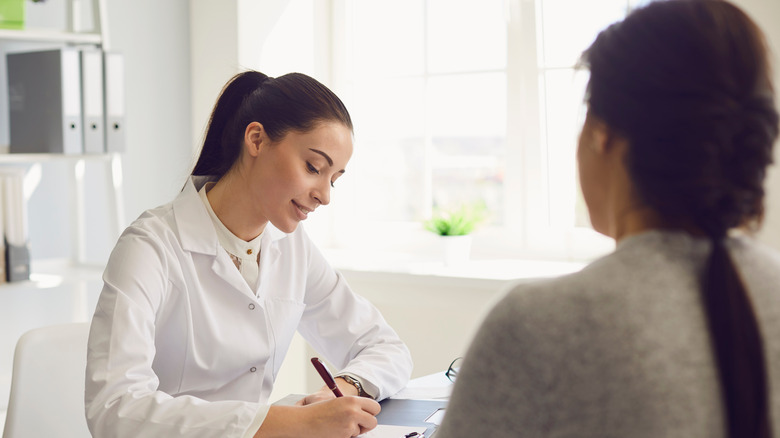 Woman in white coat consulting patient from a desk
