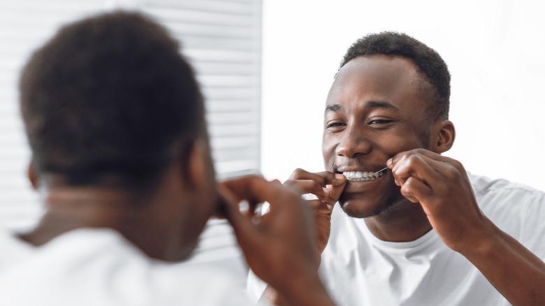 man flossing teeth in mirror